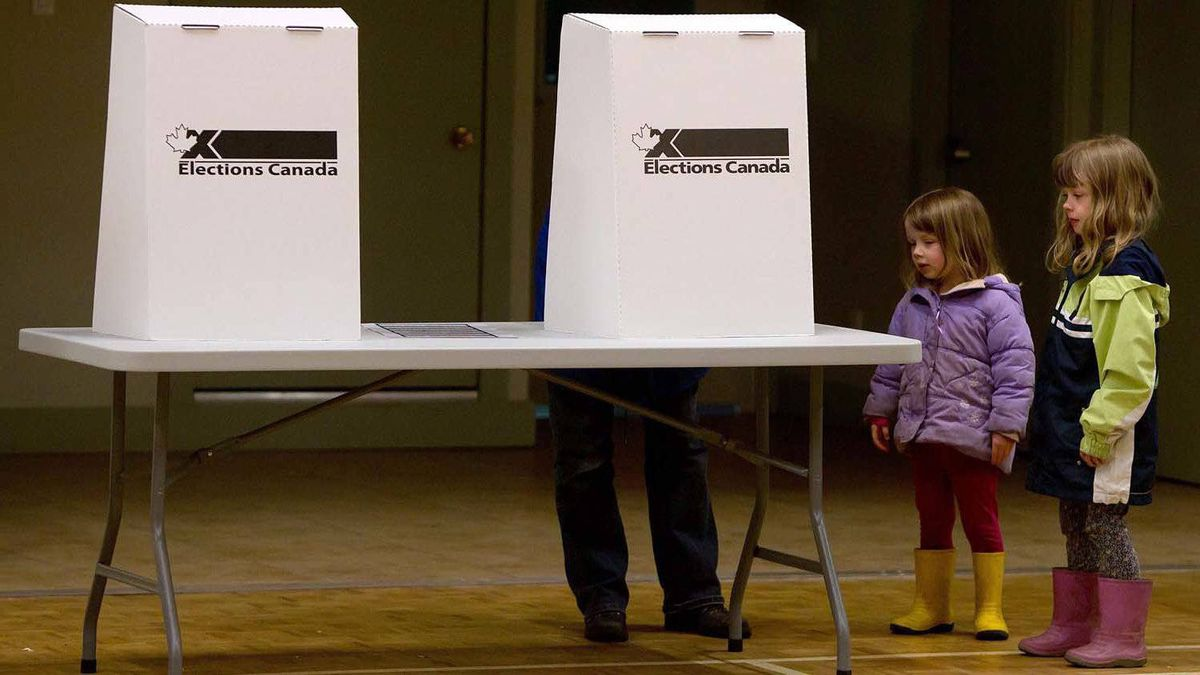 Heather Doheny, 3, second right, and her sister Megan Doheny, 5, right, wait while their mother Cathy Whalen votes in Victoria, B.C., on Monday.