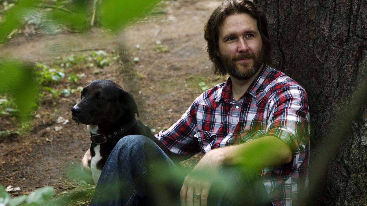 """Canadian Director Wyeth Clarkson poses for a photo with his dog, in the place where he writes, in Toronto's High Park, on June 28, 2011. His movie """"The Mountie"""" will be released on Canada Day in select Canadian theatres."""