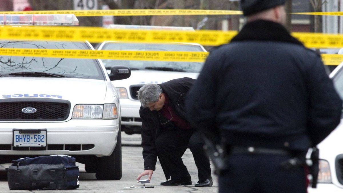 A member of the Special Investigations Unit inspects a used shell casing after a man was fatally shot by the police after allegedly threatening officers with scissors in Toronto on Feb. 3, 2012.