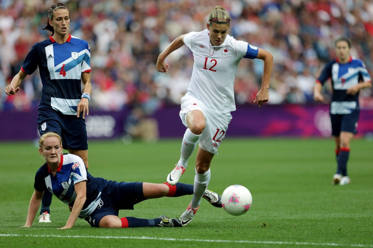 Christine Sinclair, center, avoids a tackle from Britain's Sophie Bradley.