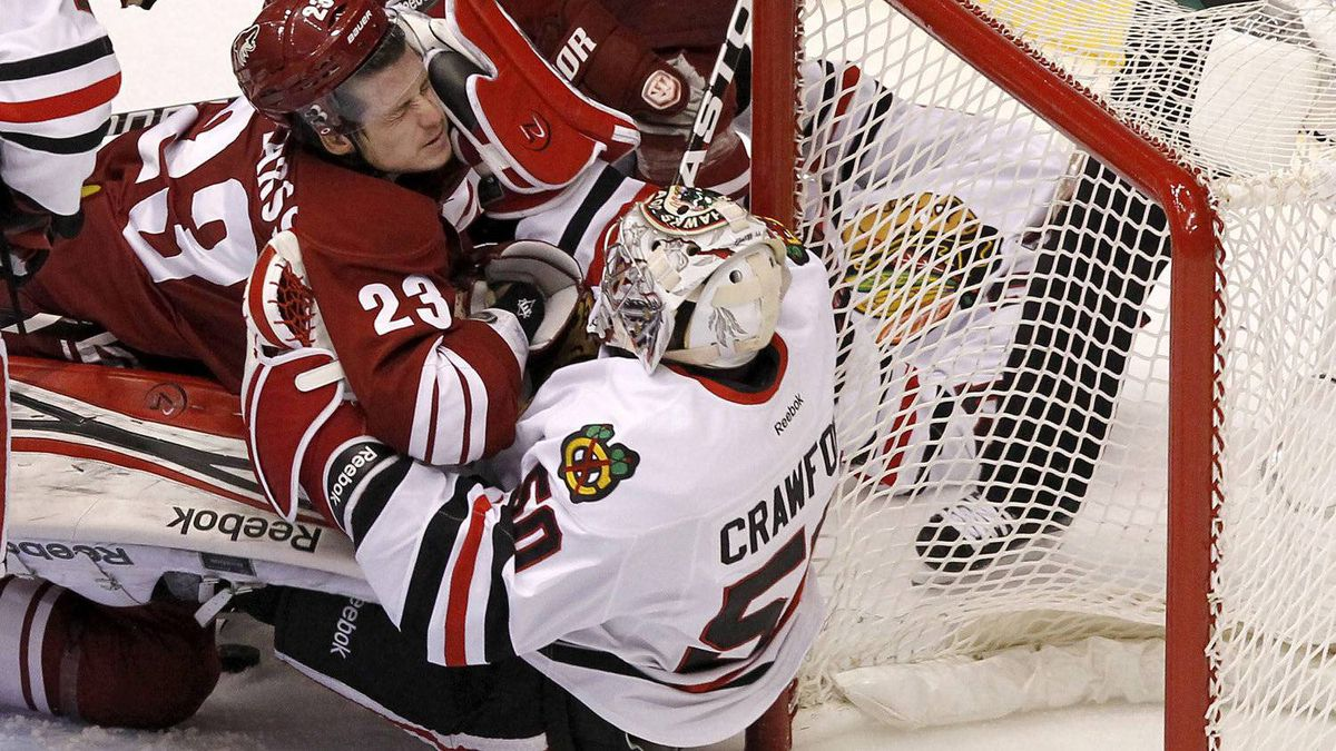 Phoenix Coyotes' Oliver Ekman-Larsson (23), of Sweden, collides with Chicago Blackhawks' Corey Crawford (50) during the first period in Game 2 of an NHL hockey Stanley Cup first-round playoff series on Saturday, April 14, 2012, in Glendale, Ariz.(AP Photo/Ross D. Franklin)