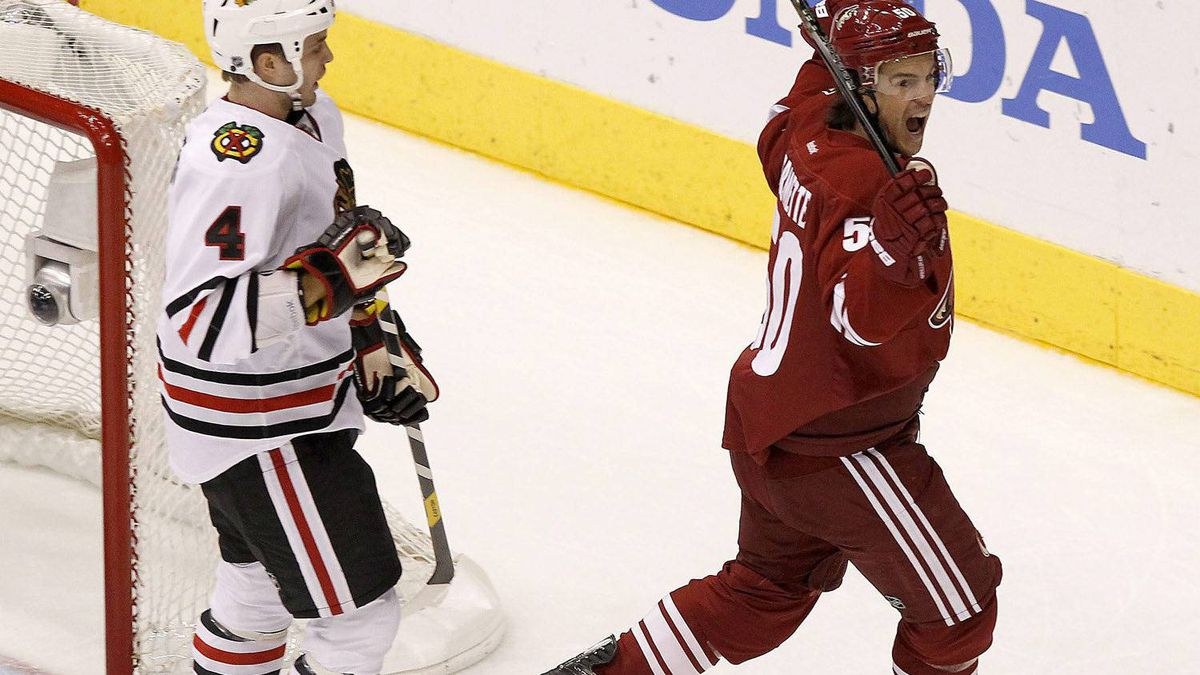 Phoenix Coyotes' Antoine Vermette, right, celebrates his goal as Chicago Blackhawks' Niklas Hjalmarsson (4), of Sweden, looks on during the first period in Game 2 of an NHL hockey Stanley Cup first-round playoff series on Saturday, April 14, 2012, in Glendale, Ariz.(AP Photo/Ross D. Franklin)