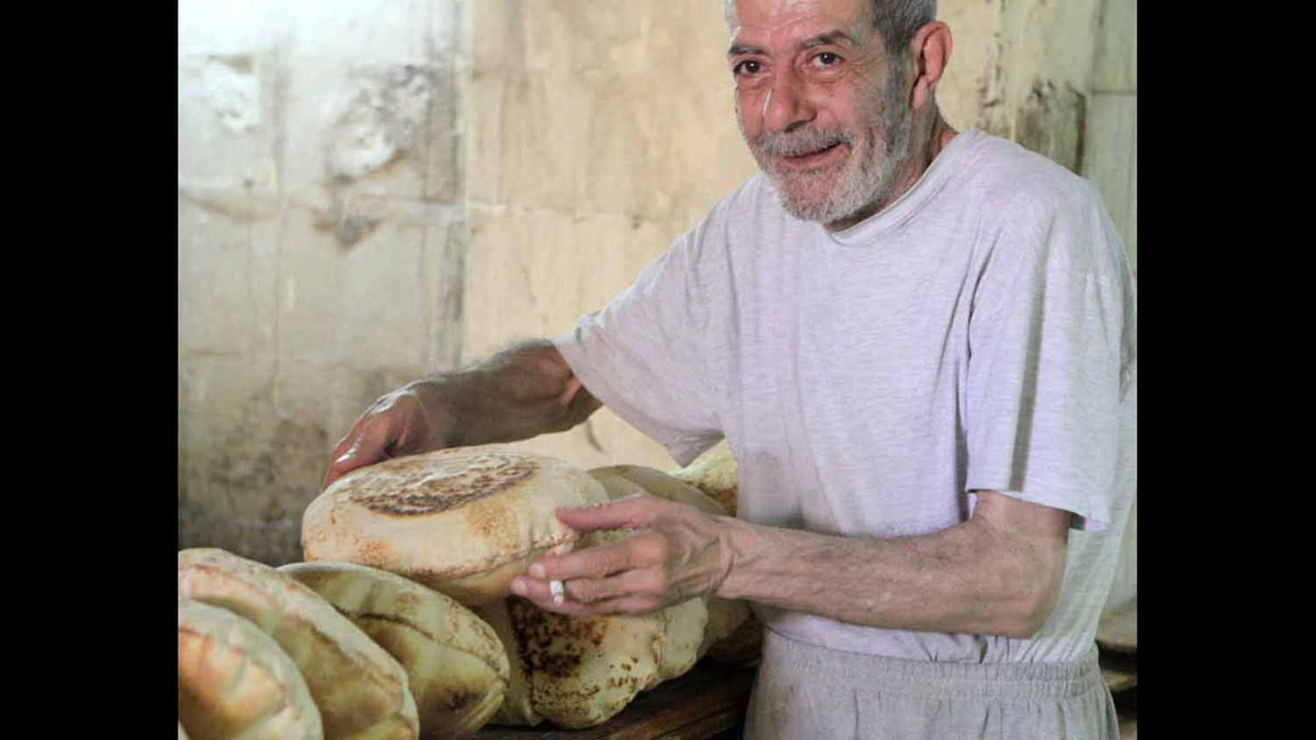 I took this photo in Lebanon April 5/12 while visiting a souk and where this man was busy making pita bread.