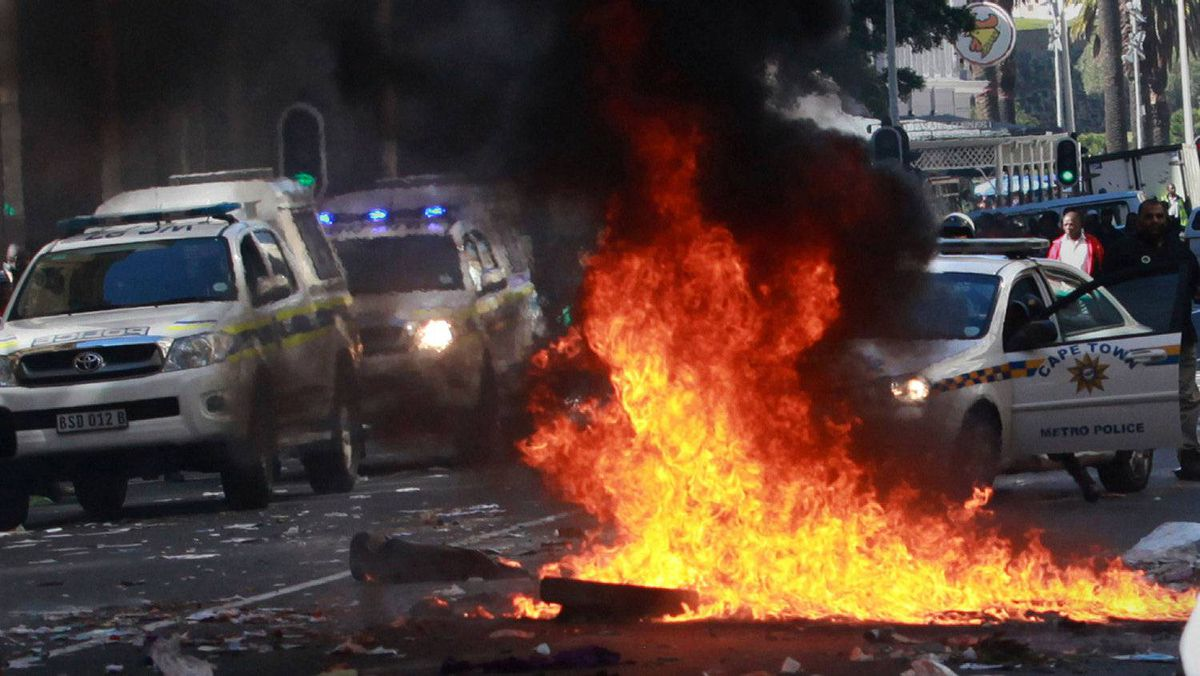 A pile of rubbish set on fire by striking municipal workers burns in Cape Town, with police vehicles in the background, on Aug. 16, 2011.