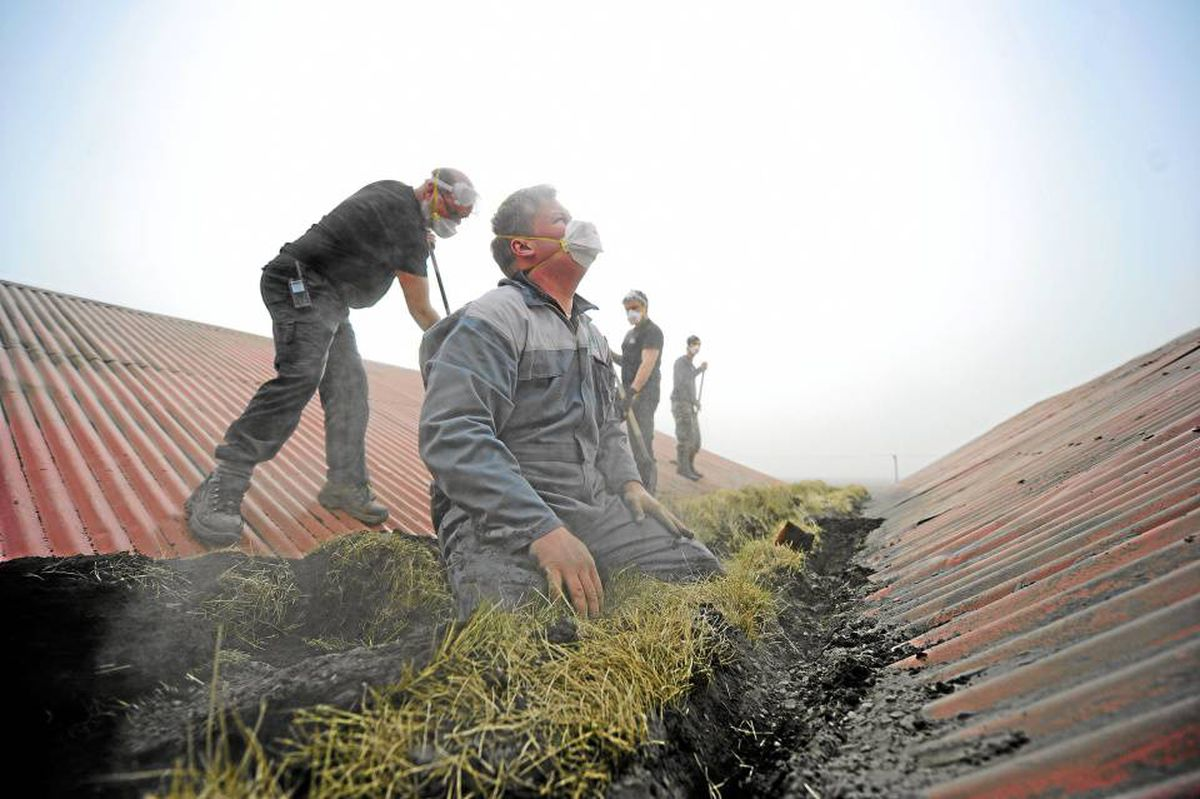 Icelandic farmers clear ash following a heavy downpour from the Eyjafjallajokull volcano this week.