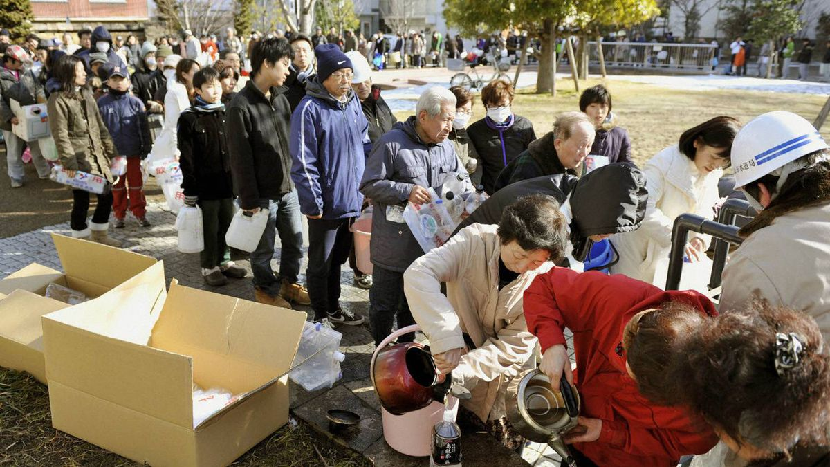People line up for drinking water at a park in Koriyama City, Fukushima Prefecture, in northeastern Japan March 12, 2011