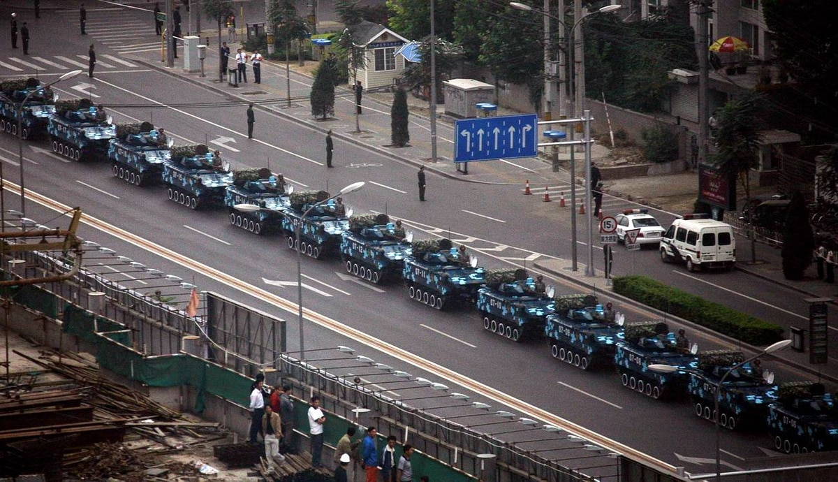 People look at military vehicles waiting in a line to drive towards Tiananmen Square as part of rehearsals for the anniversary celebrations.