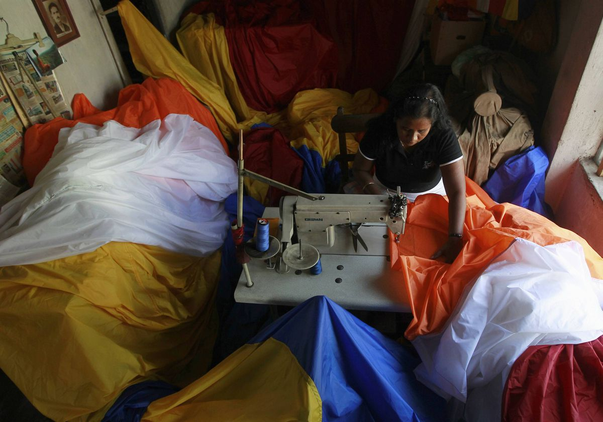 A woman stitches a large, 42 metre by 15 metre, Buddhist flag at her stall ahead of Vesak Day in Colombo. The festival commemorates the birth and enlightenment of Buddha and his attainment of Nirvana. The festival will be celebrated on May 5.