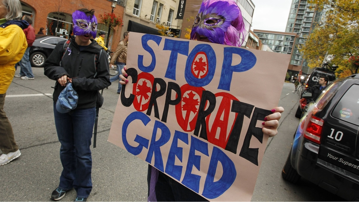 A protester holds a sign blaming corporate greed for the global economic situation during the Occupy Toronto protest on October 15, 2011.