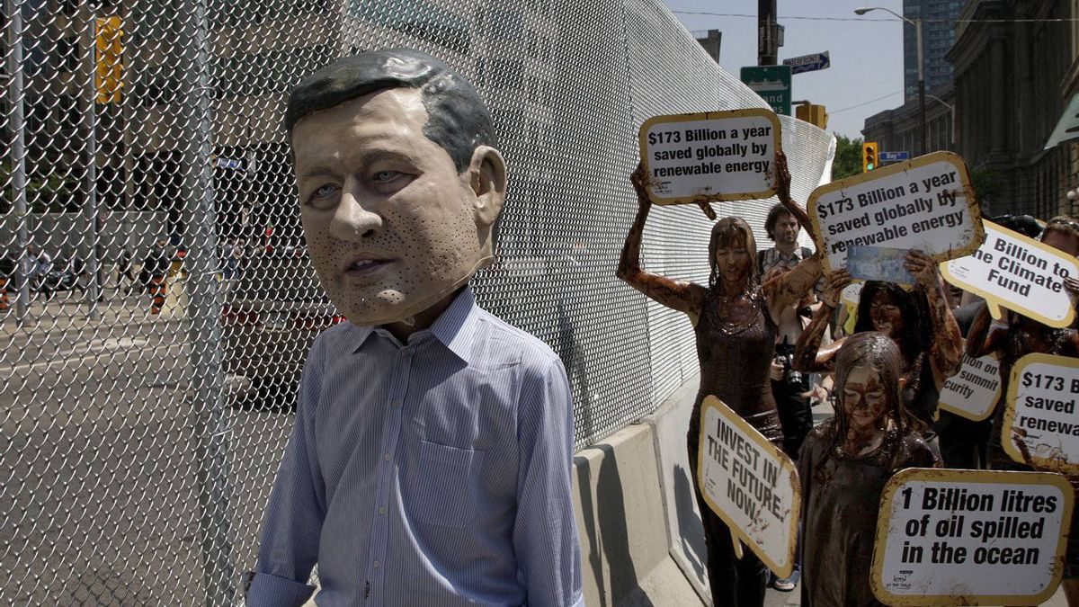 A group of protestors covered in a mix of vegetable oil and chocolate and one wearing a papier mache head depicting Canada's Prime Minister Stephen Harper, walk beside the fence built in Toronto financial district while protesting for the government spending in the G8 and G20 summit on June 17, 2010.