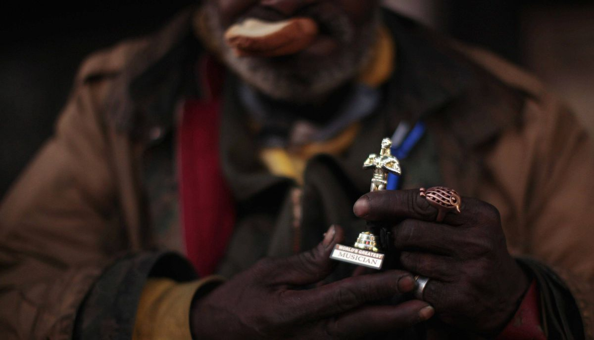 Richard McFarthing, 62, who is from Oklahoma and homeless, holds up a miniature Oscar statue as he eats a sandwich near the site of the 84th Academy Awards in Hollywood, California February 23, 2012.