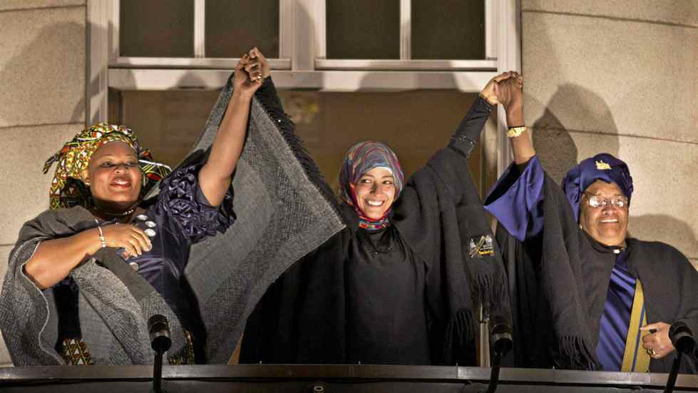 Nobel Peace Prize winners, from left, Liberian peace activist Leymah Gbowee, Tawakkol Karman of Yemen, and Liberian president Ellen Johnson-Sirleaf hold hands in solidarity from the balcony of the Grand Hotel during a torchlight procession in their honor in Oslo, Norway, Dec. 10, 2011.
