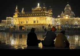 Sikhs sit near the illuminated Golden Temple on the eve of the anniversary of the birth of Guru Gobind Singh, the tenth Sikh Guru, in Amritsar, India.