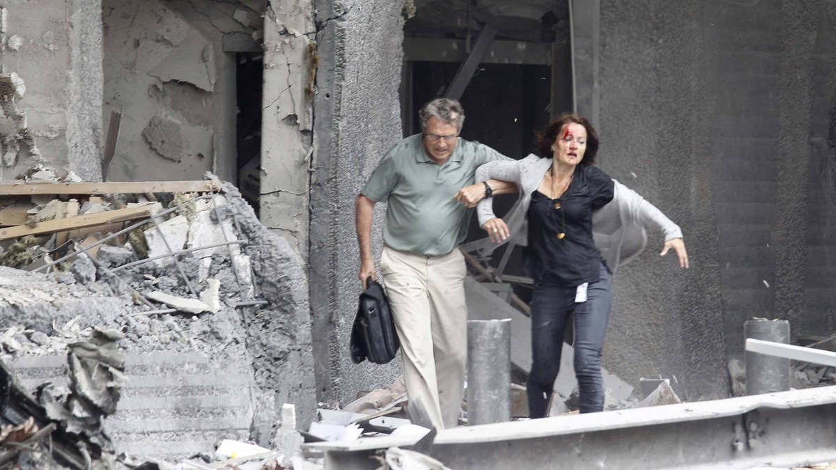 An injured woman is helped by a man at the scene of a powerful explosion that rocked central Oslo July 22, 2011.
