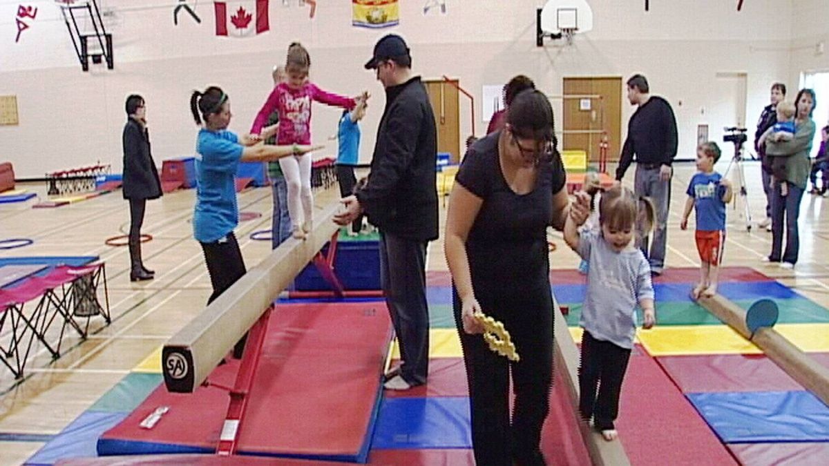 Parents accompany their children on balance beams during a Tumble Tots class.