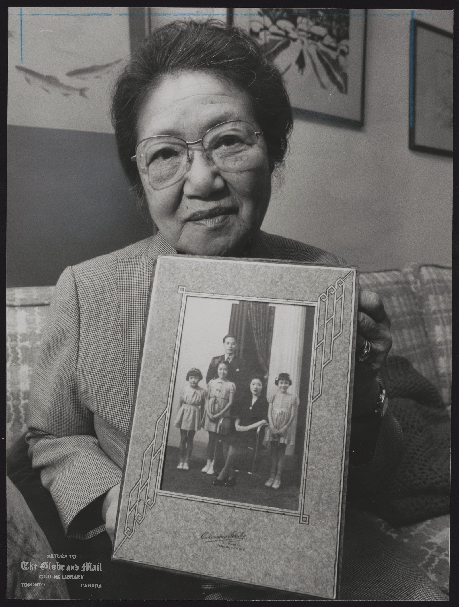 JAPANESE IN CANADA Mrs. Umezuki with family photo taken a year before internment. [Redress for Japanese: can knot be untangled? In 1942 her husband was sent to Rainbow in the interior of British Columbia to work on a road camp. In need of money, Mrs. Umezuki sold the family dry-cleaning business and took her three daughters to an internment camp in Tashme, B.C., 100 miles from the Pacific coast. They lived in a barn-like structure and were soon joined by Mr. Umezuki who labored at Tashme for 25 cents an hour.]