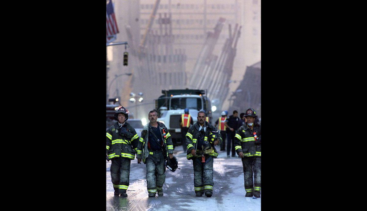 Firefighters walk up Chrich Street and away from the remains of the World Trade Center towers in New York, early Sept. 12, 2001.