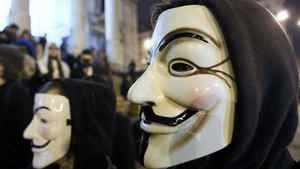 """A protester wearing a Guy Fawkes mask, symbolic of the hacktivist group """"Anonymous"""", takes part in a protest in central Brussels January 28, 2012."""