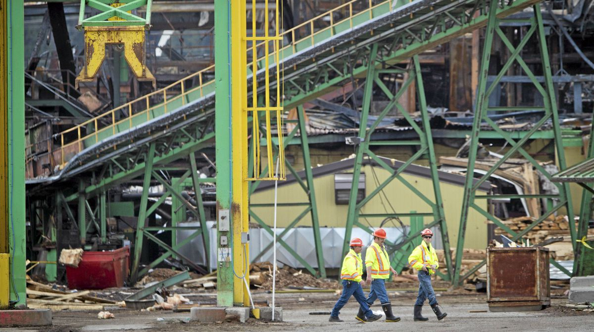 Inspectors at the Lakeland Sawmill in Prince George look over the site on April 25, 2012, after a fire and explosion at the facility.