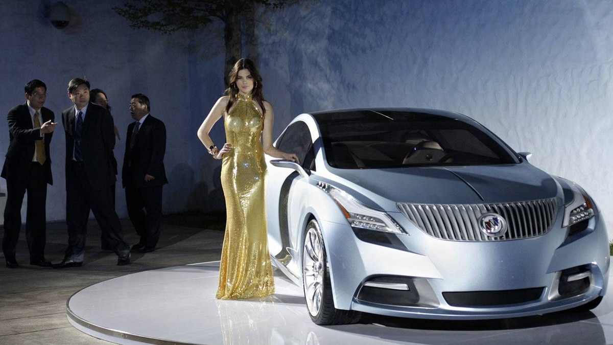 A model stands next to a Buick Riviera at the Auto China 2008 auto show in Beijing in 2008.