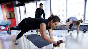 The Morning Show news anchor Kris Reyes, left, along with host Liza Fromer, right, workout with personal trainer Ray Ortiz at the Global TV studio in Toronto. Because of their their busy schedules, the trainer comes to the studio to lead the workout sessions twice a week after the show.