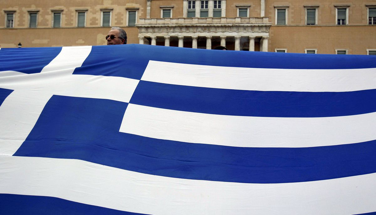 A demonstrator is seen behind a giant Greeek flag during protests against planned reforms by Greece's coalition government in Athens, February 10, 2012.