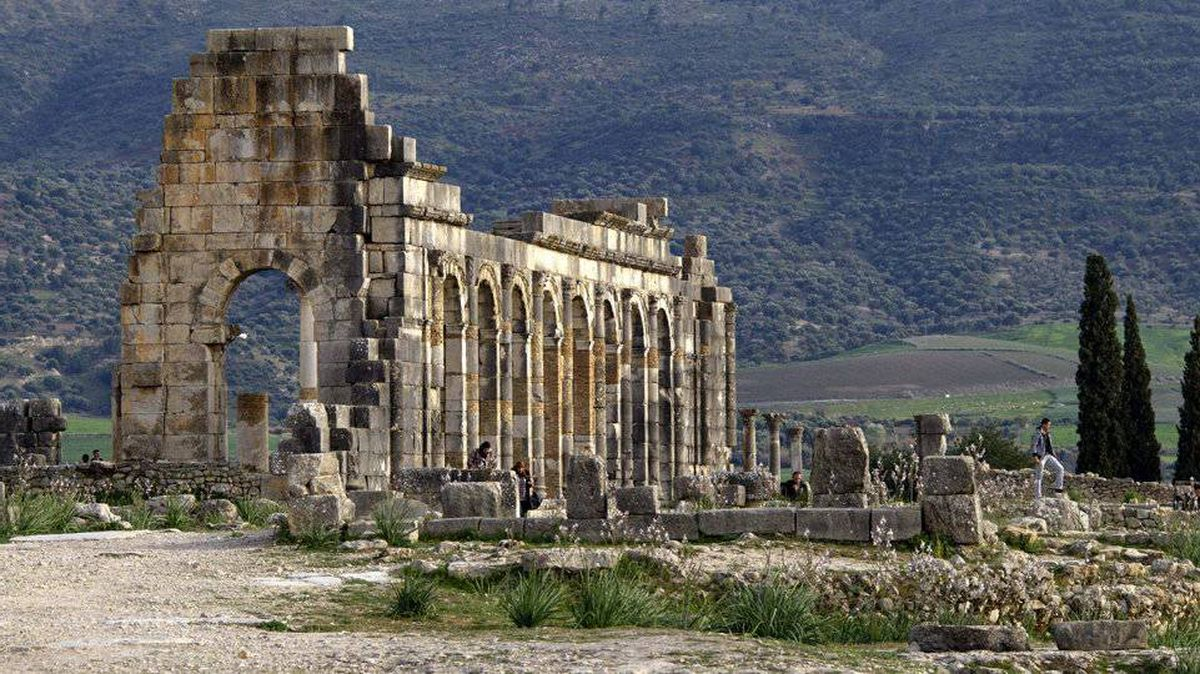 The afternoon sun shines on the arches of the Basilica, the main administrative building in the ancient Roman city of Volubilis, near Meknes, Morocco.