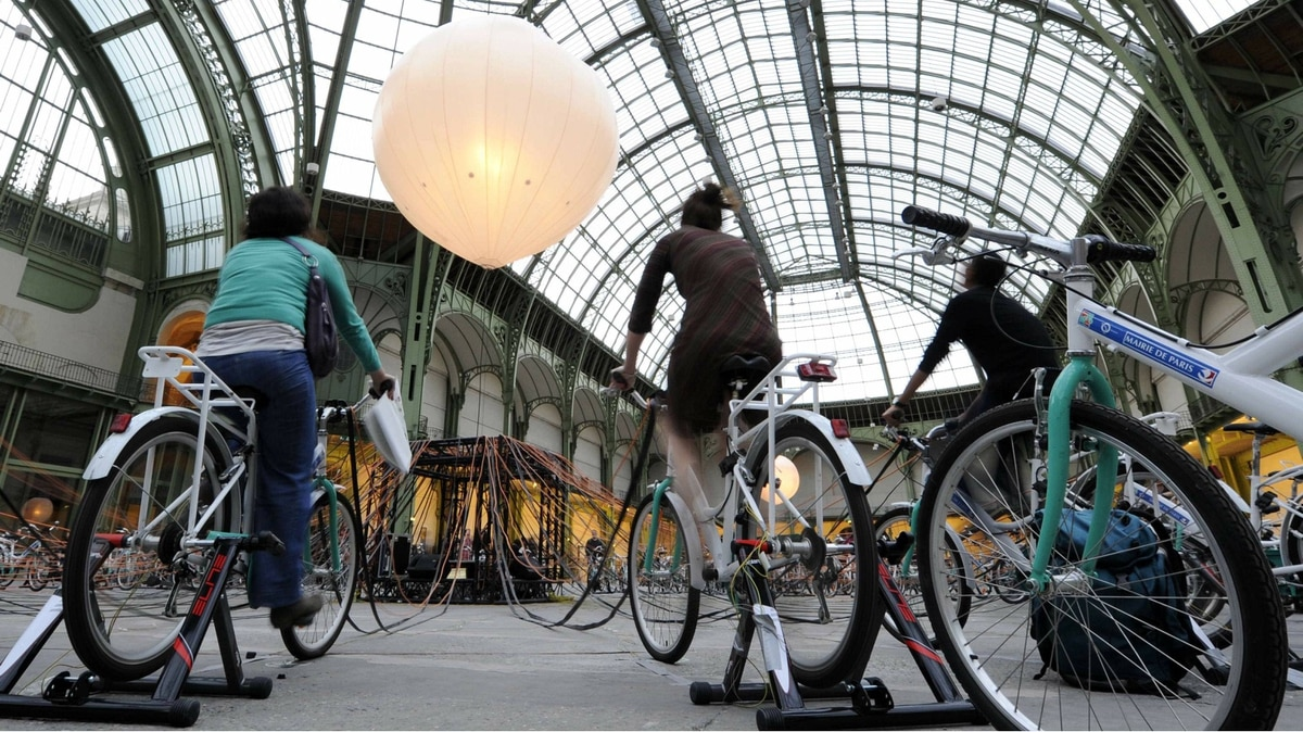 People pedal on bicycles equipped with dynamos which light up gigantic luminous bulbs as they participate an interactive installation, during the European heritage days at the Grand Palais in Paris September 17, 2011.