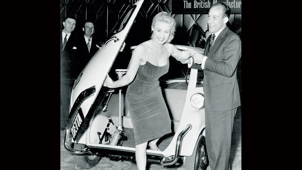 British racing driver Stirling Moss, who always had an eye for the ladies, helps extract one from an Isetta at the British Motor Show in the 50s.