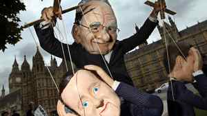 A demonstrator dressed in a Rupert Murdoch mask controls puppets of British Prime Minister David Cameron (foreground) and British Minister for Culture, Media and Sport Jeremy Hunt, (right) during a protest against Mr. Murdoch's proposed takeover of BSkyB.