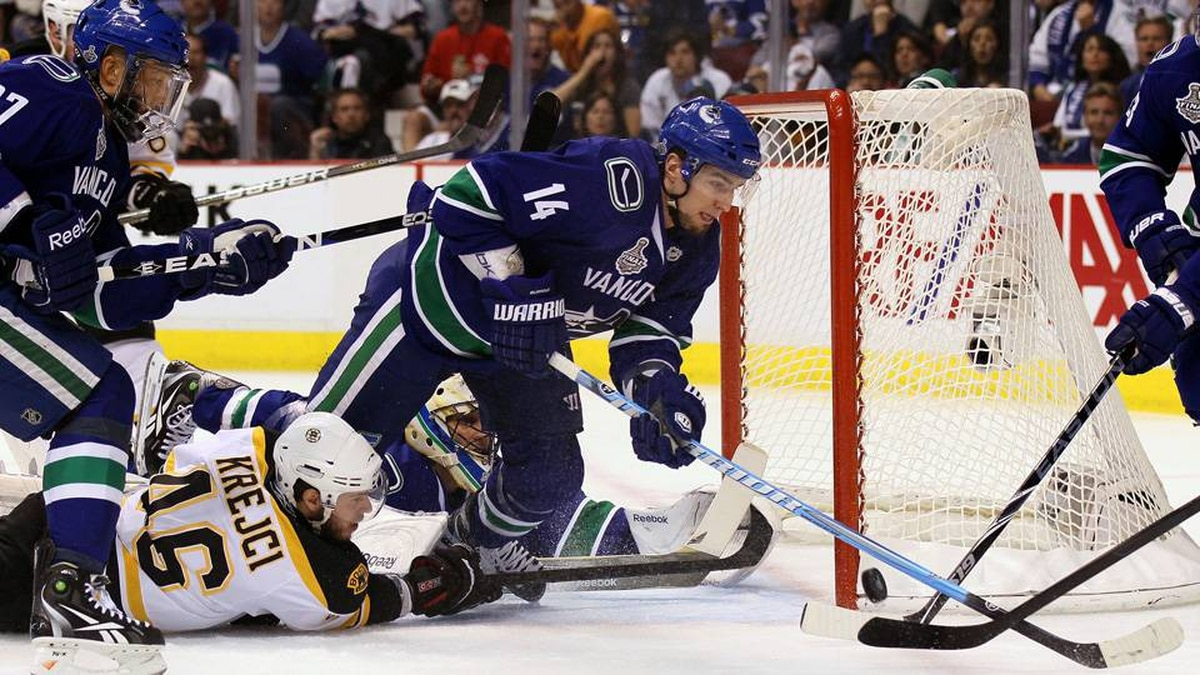 Alex Burrows of the Vancouver Canucks fights for the puck against the Boston Bruins during Game 7.