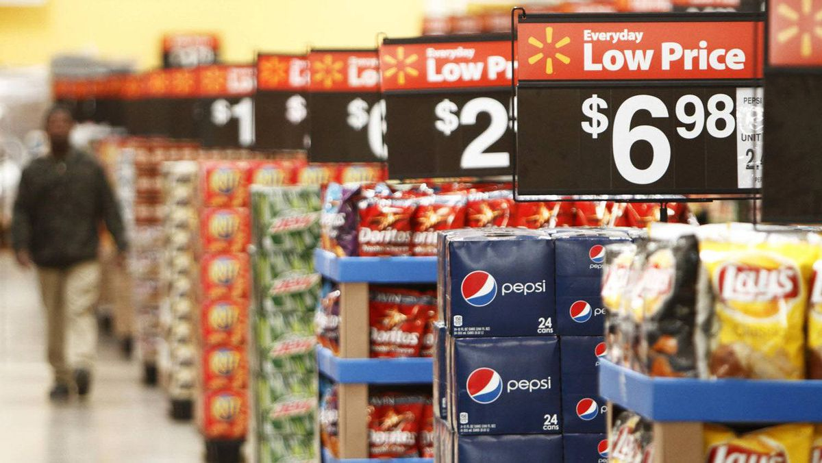 """A worker walks through the """"Action Alley"""" at a new Wal-Mart store in Chicago, in this January 24, 2012 file photo."""