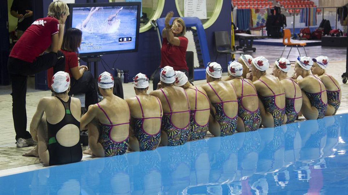 The swimmers huddle in front of a television screen several times of day to view video of their performance, as head coach Julie Sauvé instructs them on corrections.