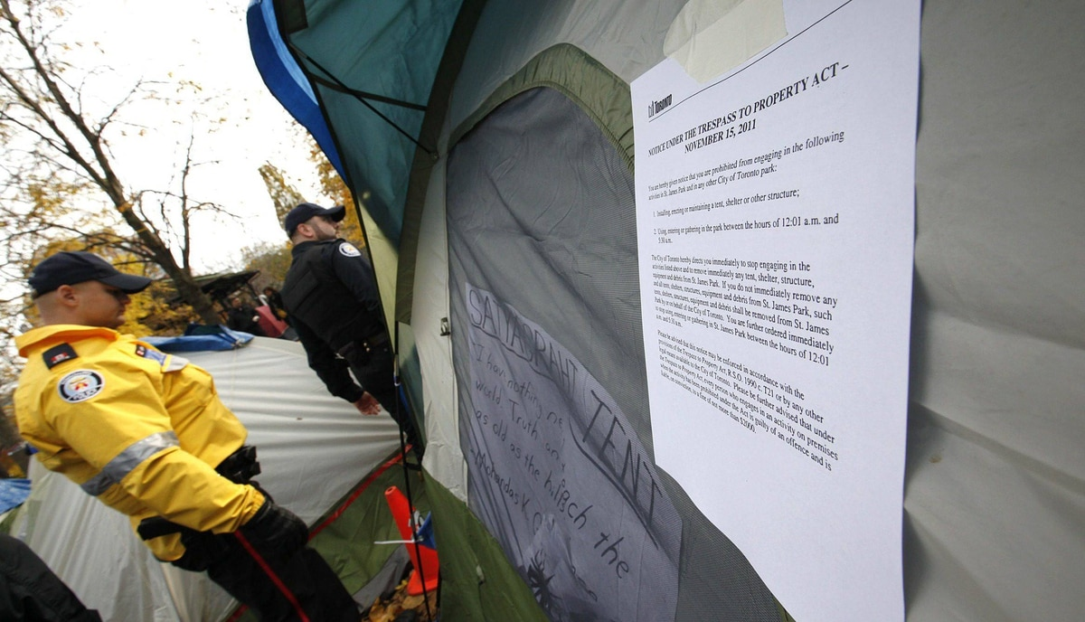 City of Toronto By-Law officers escorted by Toronto Police service post an eviction and trespass notice in the Occupy Toronto Camp at St. James Park in Toronto.