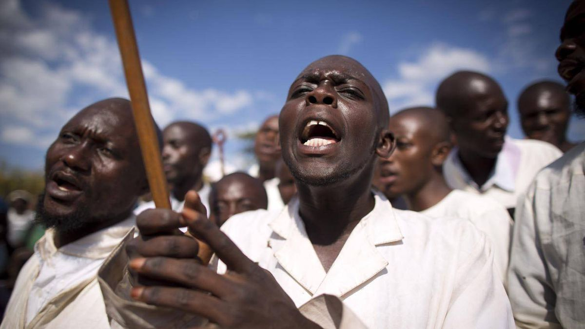 A choir sings as a priest baptizes the faithful in a river outside Lubumbashi.