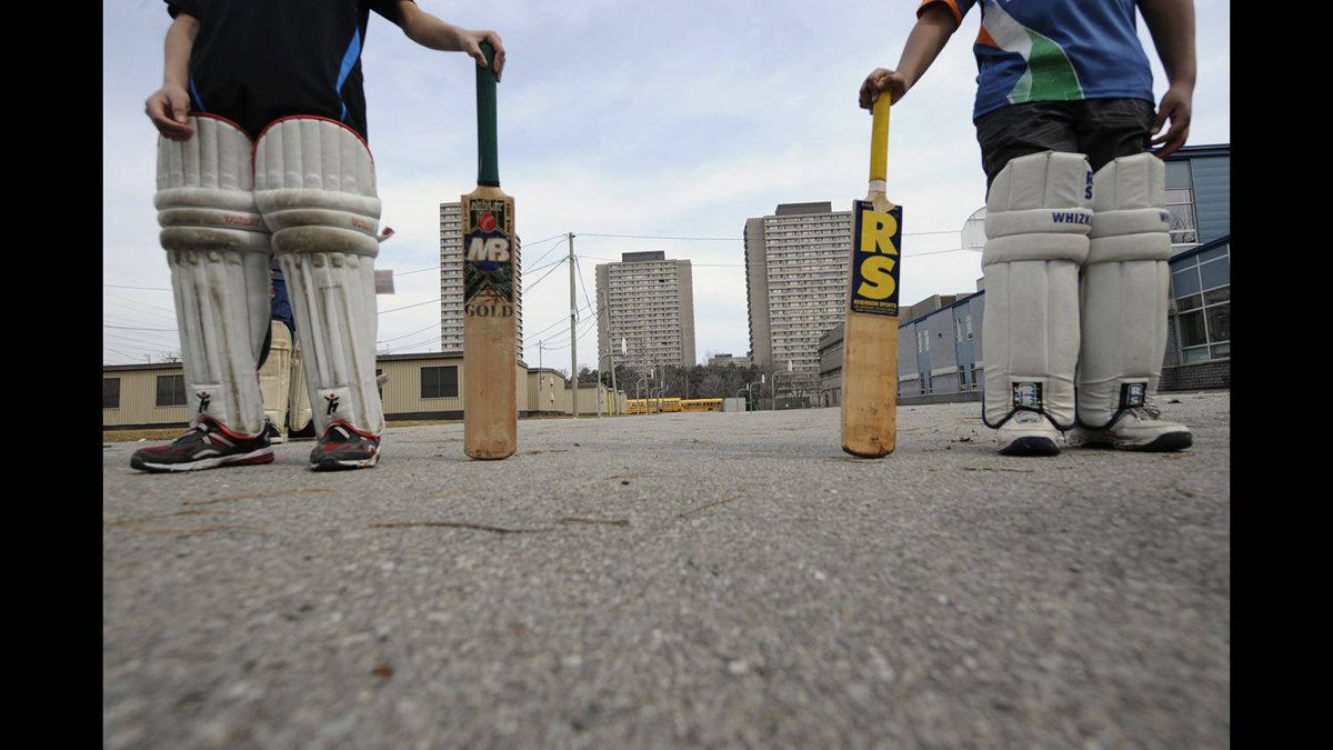 Eleven-year-old Saad Nandhla, left, and 12-year-old Ebrahim Tagari, stand with their cricket bats at hand. What is currently a field with portables behind Valley Park Middle School will soon become a cricket oval. I'd been assigned to illustrate a story on how one Toronto community was going ahead with a project that would give the local immigrant community something to call their own. In the large field of an elementary school, people were planning on building a cricket pitch, a sport the largely South Asian community follows passionately. Unfortunately, it was March and the grassy field was muddy and wet. I made the best photographs I could in those conditions. I also needed other photos in case these didn't quite work. Since the area was high-density with large apartment complexes, I had to work these into the photograph to illustrate the need the community had for a place where they could get together, enjoy a sport they grew up playing and get outside to do something physical. This is an unusual portrait in that the heads are cut out of the photograph. I had photographed them head to toe as well, but this composition seemed to work best for me. It made it less ethnicity-specific and more symbolic of inner-city youth, their environment and how that space can be adapted to their needs. The bleakness of an asphalt and concrete world can be overcome when everyone involved works towards an attainable goal.