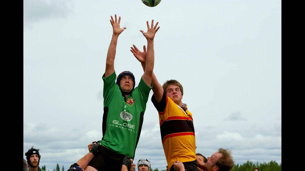 Two rugby players reach for the ball during a line-out. Edson, AB.