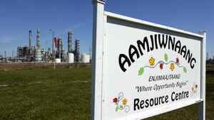 A sign for the Aamjiwnaang First Nation Resource Centre is located across the road from a chemical plant in Sarnia, Ont.