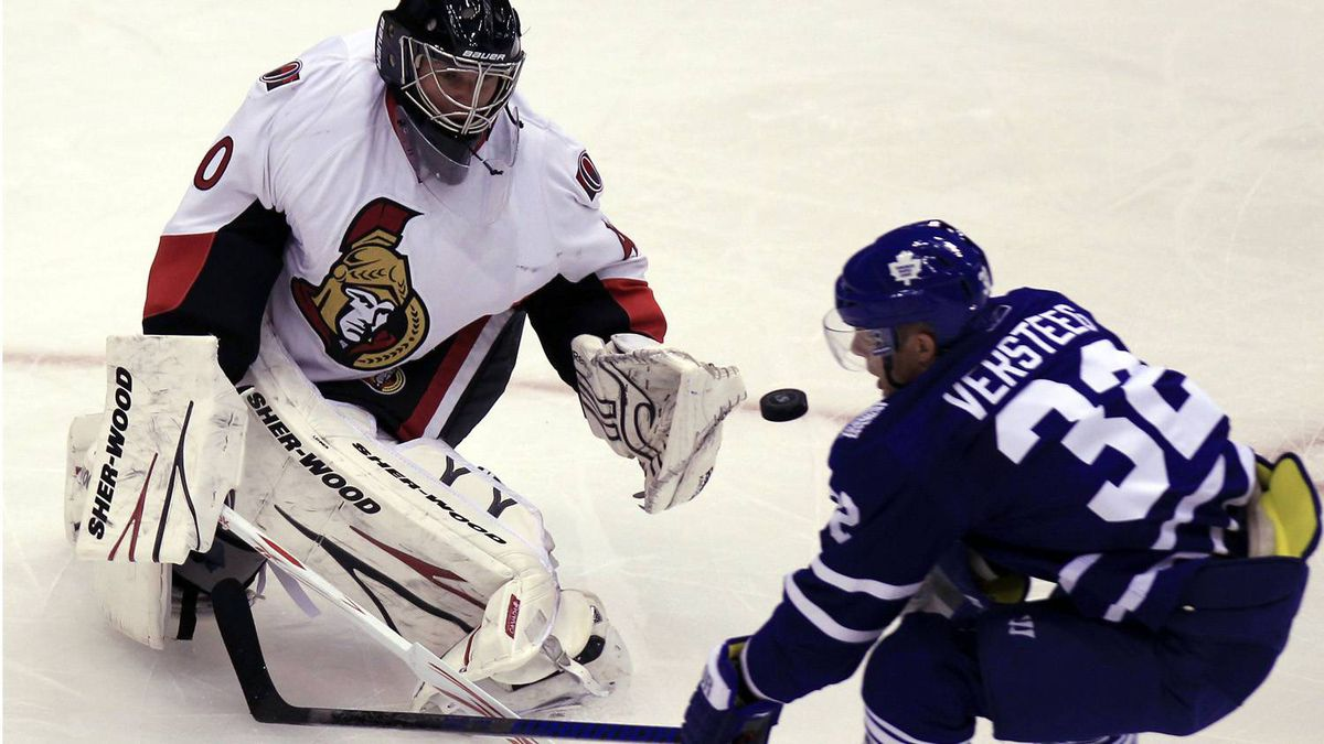 Ottawa Senators goalie Robin Lehner (L) knocks the puck away from Toronto Maple Leafs forward Kris Versteeg (R) during the first period of their NHL pre-season hockey game in Toronto September 21, 2010.