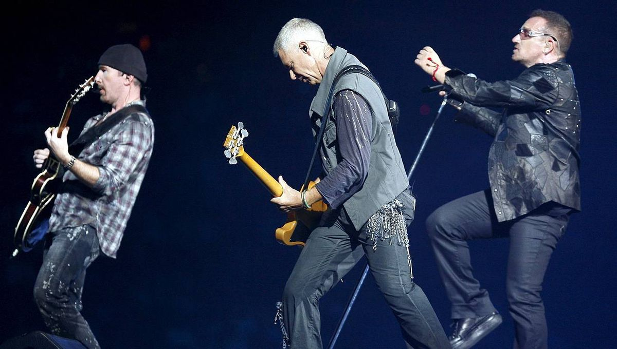 Lead singer Bono of the rock band U2 performs with guitarist The Edge and bass guitarist Adam Clayton at Giants Stadium in East Rutherford