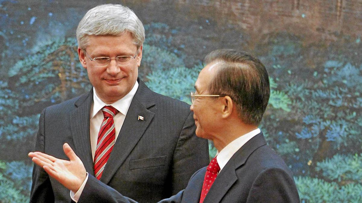 Canada's Prime Minister Stephen Harper looks on as Chinese Premier Wen Jiabao gestures (R) after a signing ceremony at the Great Hall of the People in Beijing Feb. 8, 2012.
