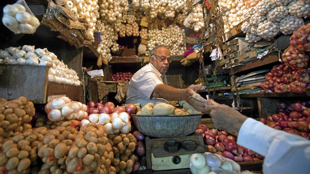 A vendor exchanges money with a customer at a shop selling garlic, onions and potatoes at a wholesale market in Mumbai, April 28, 2011.