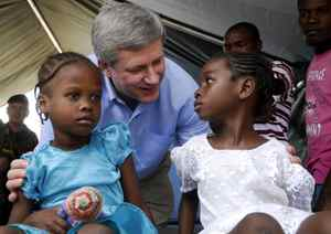 Prime Minister Stephen Harper greets two Haitian girls on Feb. 16, 2010 during a visit to a Canadian Army field hospital in Jacmel.