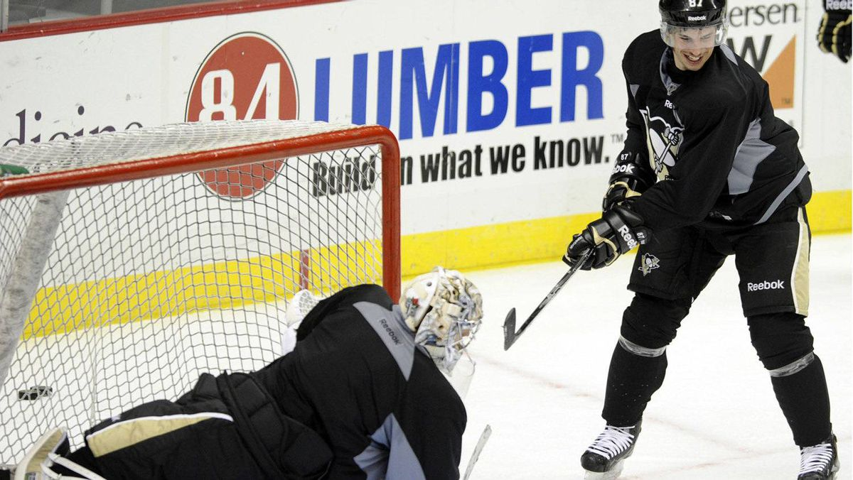"""The Pittsburgh Penguins' Sidney Crosby (R) shoots on teammate Marc-Andre Fleury (29) during the """"morning skate"""" in preparation for Crosby's return to action Monday night against the New York Islanders in Pittsburgh, Pennsylvania, November 21, 2011. REUTERS/David DeNoma"""
