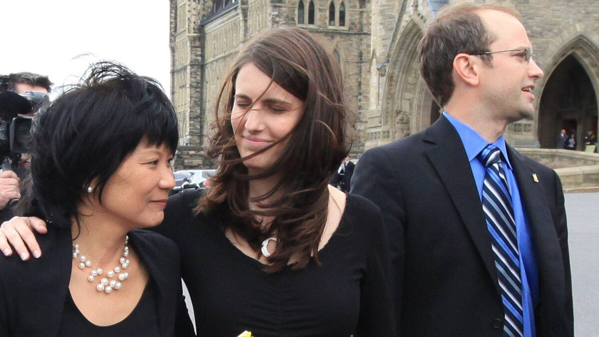 Olivia Chow, wife of NDP Leader Jack Layton, along with stepdaughter Sarah Layton and stepson Mike Layton (left to right) acknowledge members of the public as they wait in line to pay their respects to her husband.