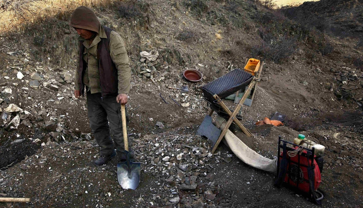 A small-scale miner rests on his shovel next to equipment as he takes a break from digging for gold on a small hill overlooking grasslands located around 200 km south-west of the Mongolian capital city Ulan Bator.