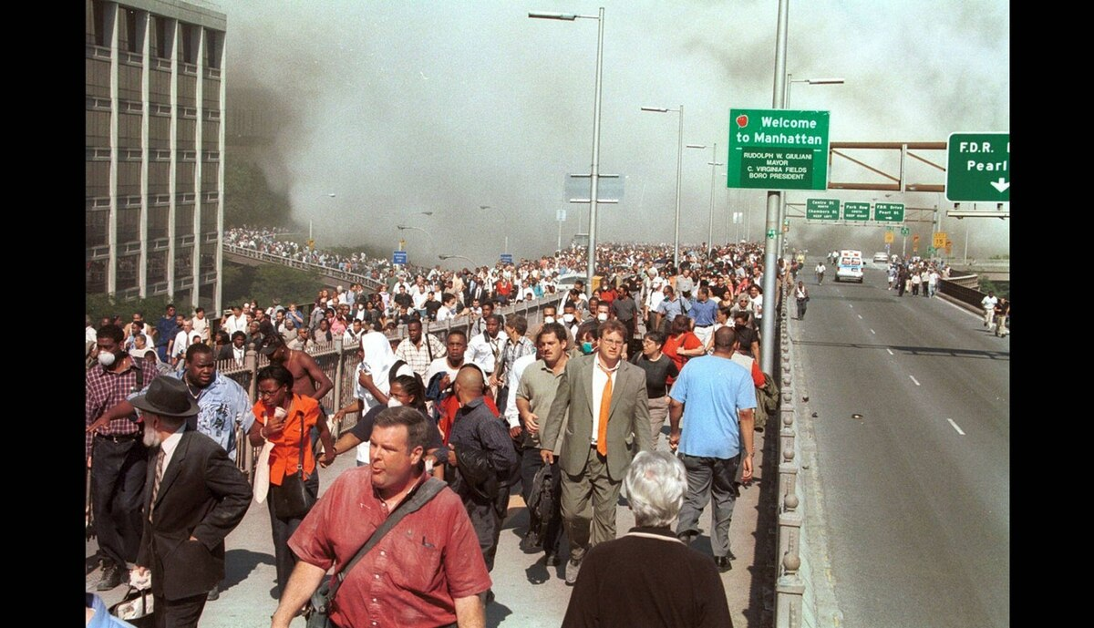 People flee lower Manhattan across the Brooklyn Bridge in New York, Tuesday, Sept. 11, 2001, following a terrorist attack on the World Trade Center.