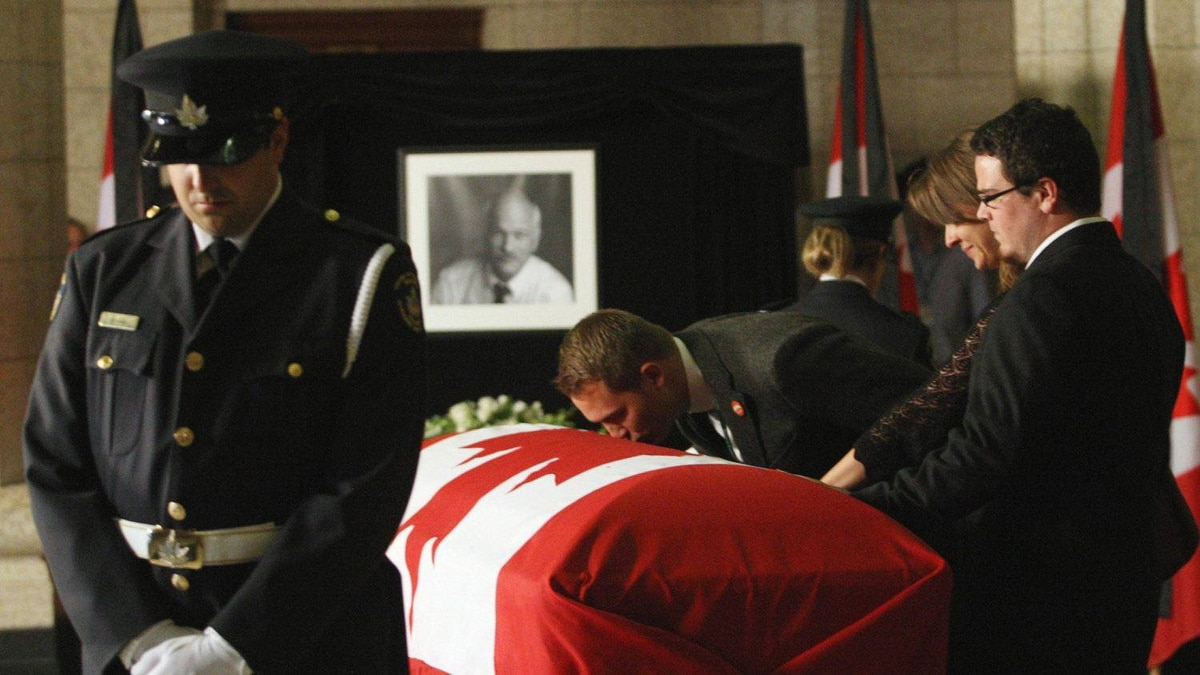 A man leans over to kiss the casket of Mr. Layton.