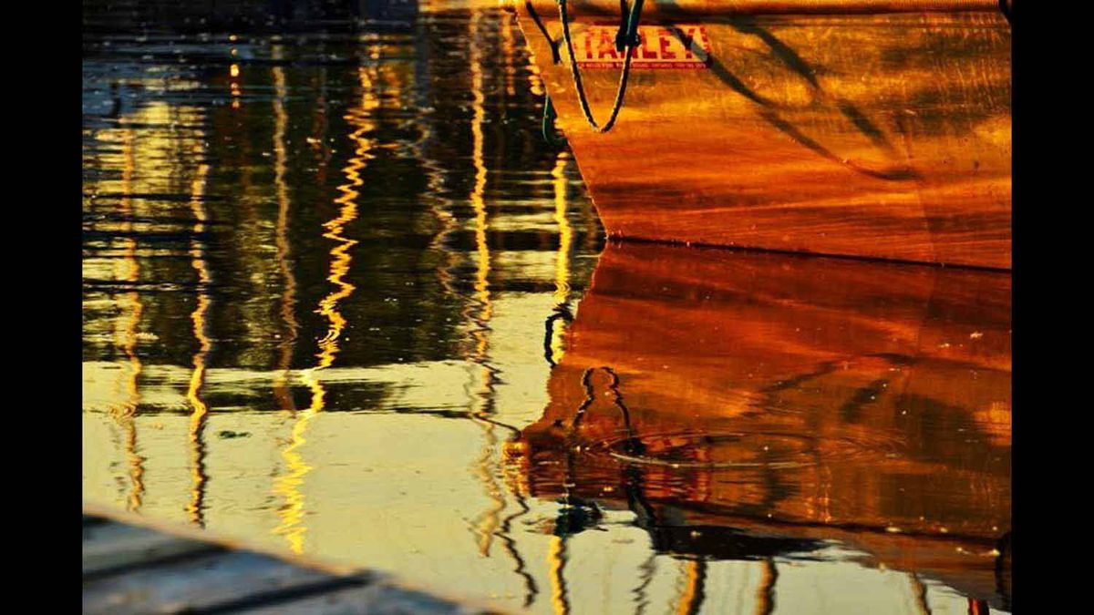 This picture was taken of an old boat at the Marina. I appreciated the sun setting and it's reflection in the water. Taken with Nikon D7000 in June 2011