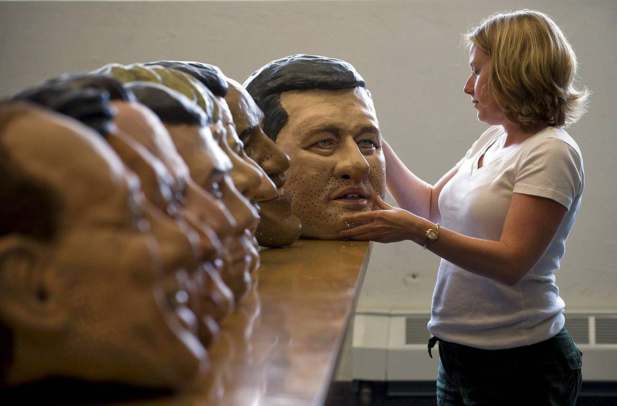 Karen Palmer of Oxfam Canada inspects a Stephen Harper papier mache head at their Toronto office, on Monday, June 14, 2010. Barack Obama's ear is chipped, but his and other world leaders' giant papier mache heads have arrived in Canada otherwise intact.